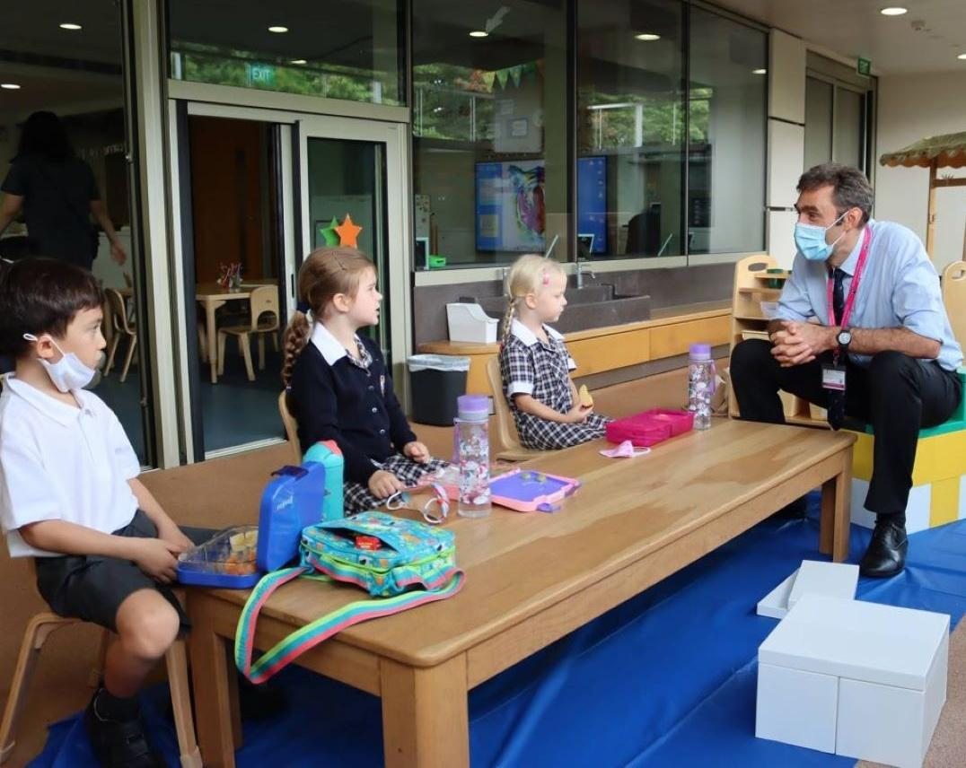 Head Master Paul Wilson talks with pupils over lunch at Brighton College Singapore